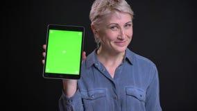 Retrato del primer de la hembra caucásica atractiva usando la tableta y mostrar la pantalla verde a la sonrisa de la cámara almacen de video