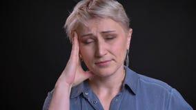 Retrato del primer de la hembra caucásica cansada y enfadada que consigue una sensación del dolor de cabeza enferma y que frota s almacen de video