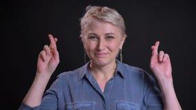 Retrato del primer de la hembra caucásica esperanzada que hace sus fingeres cruzar y que ruega metrajes