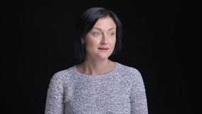 Retrato del primer de la hembra caucásica hermosa adulta con el pelo negro corto que consigue mirada sonriente tímida y torpe del almacen de metraje de vídeo