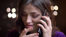 Retrato del primer de la hembra caucásica hermosa joven que habla en el teléfono que ríe y que cubre su boca con una entrega metrajes