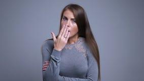 Retrato del primer de la hembra caucásica joven enferma que tose y que se siente mal con el fondo aislado en gris almacen de metraje de vídeo