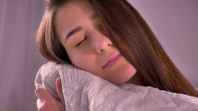 Retrato del primer de la hembra caucásica joven que abraza una almohada mientras que mira la cámara en el dormitorio dentro almacen de video