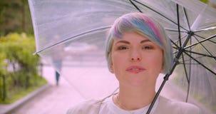 Retrato del primer de la hembra caucásica linda joven con el pelo teñido que sostiene un paraguas que mira la cámara que fija su  almacen de metraje de vídeo