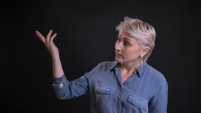 Retrato del primer de la hembra caucásica de mediana edad que señala con su mano a la derecha que presenta un proyecto con almacen de video