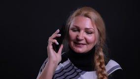 Retrato del primer de la hembra cauc?sica de mediana edad que tiene una llamada de tel?fono con el fondo aislado en negro metrajes