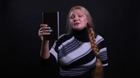 Retrato del primer de la hembra cauc?sica de mediana edad que tiene una llamada video en la tableta con el fondo aislado en negro almacen de video
