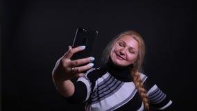 Retrato del primer de la hembra cauc?sica de mediana edad que toma selfies en el tel?fono con el fondo aislado en negro almacen de metraje de vídeo