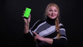 Retrato del primer de la hembra cauc?sica de mediana edad usando el tel?fono y mostrar la pantalla verde a la c?mara con el fondo almacen de video
