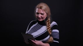 Retrato del primer de la hembra cauc?sica de mediana edad usando la tableta con el fondo aislado en negro almacen de metraje de vídeo
