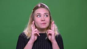 Retrato del primer de la hembra cauc?sica rubia bonita joven que hace sus fingeres cruzar con esperanza con el fondo aislado almacen de metraje de vídeo