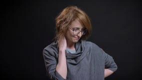 Retrato del primer de la hembra de mediana edad atractiva que consigue sonrisa tímida y torpe con el fondo aislado en negro almacen de metraje de vídeo