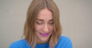 Retrato del primer de la hembra morena linda joven con la barra de labios púrpura que sonríe alegre presentando delante de la cám metrajes