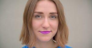 Retrato del primer de la hembra morena de pelo corto joven con la barra de labios púrpura que sonríe feliz presentando delante de metrajes