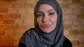 Retrato del primer de la hembra musulmán atractiva adulta en el hijab que es feliz mirando la cámara y sonriendo alegre dentro metrajes