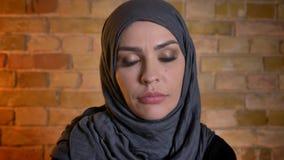 Retrato del primer de la hembra musulmán atractiva adulta en el hijab que mira la cámara dentro en un apartamento acogedor metrajes