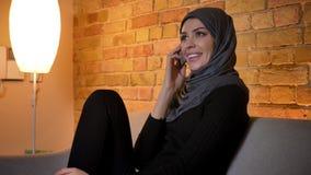 Retrato del primer de la hembra musulmán atractiva adulta en el hijab que tiene una llamada de teléfono mientras que se sienta en almacen de video