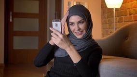 Retrato del primer de la hembra musulmán atractiva adulta en el hijab que tiene una llamada video en el teléfono mientras que se  metrajes
