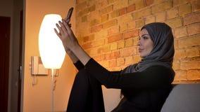 Retrato del primer de la hembra musulmán atractiva adulta en el hijab que tiene una llamada video en el teléfono mientras que se  almacen de metraje de vídeo