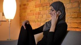 Retrato del primer de la hembra musulmán atractiva adulta en hijab que habla en el teléfono y que sonríe alegre mientras que se s metrajes