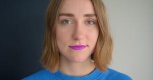 Retrato del primer de la hembra de pelo corto joven con la barra de labios púrpura atractiva que sonríe mirando la cámara aislada almacen de metraje de vídeo