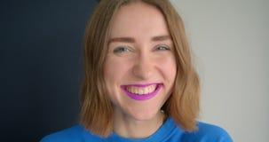 Retrato del primer de la hembra de pelo corto joven con la barra de labios púrpura atractiva que sonríe y que ríe feliz la mirada almacen de metraje de vídeo