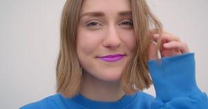 Retrato del primer de la hembra de pelo corto joven con la barra de labios púrpura que fija su pelo que mira el fondo de la cámar almacen de metraje de vídeo