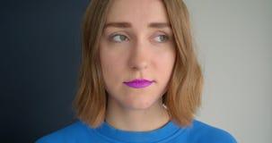 Retrato del primer de la hembra de pelo corto joven con la barra de labios púrpura que mira el fondo aislado cámara metrajes