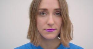 Retrato del primer de la hembra de pelo corto joven con la barra de labios púrpura que mira el fondo de la cámara aislado en blan almacen de metraje de vídeo