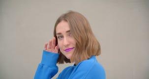 Retrato del primer de la hembra de pelo corto joven con la barra de labios púrpura que sonríe feliz presentando delante de la cám metrajes