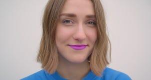 Retrato del primer de la hembra de pelo corto joven con la barra de labios púrpura que sonríe mirando el fondo de la cámara aisla metrajes