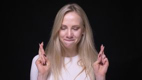 Retrato del primer de la hembra rubia bonita joven que hace sus fingeres cruzar ansiosamente mirando la cámara con el fondo metrajes