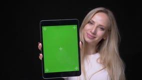 Retrato del primer de la hembra rubia bonita joven usando la tableta y mostrar la pantalla verde de la croma que mira la cámara c almacen de metraje de vídeo