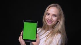 Retrato del primer de la hembra rubia bonita joven usando la tableta y mostrar la pantalla verde que mira la cámara con almacen de video