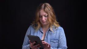 Retrato del primer de la hembra rubia caucásica adulta que mecanografía en la tableta delante de la cámara con el fondo aislado almacen de metraje de vídeo