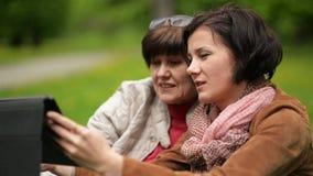 Retrato del primer de la madre bonita y de la hija madura que usa la tableta junto al aire libre Dos mujeres morenas están mirand almacen de metraje de vídeo