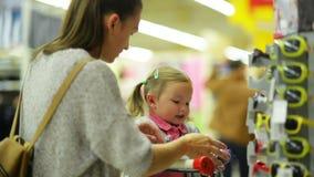 Retrato del primer de la madre joven atractiva con su pequeña hija en el supermercado Familia feliz que elige almacen de metraje de vídeo
