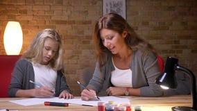 Retrato del primer de la madre joven y de su dibujo de la hija y tiempo del gasto junto Mamá que enseña una muchacha a cómo dibuj almacen de metraje de vídeo