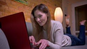 Retrato del primer de la mensajería femenina de la morenita caucásica atractiva joven en el ordenador portátil y de la mentira en almacen de video