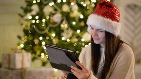 Retrato del primer de la morenita linda con la tableta en sus manos en fondo del árbol de navidad Opinión la muchacha emocional e almacen de video
