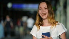 Retrato del primer de la muchacha adolescente con el pasaporte y del boleto en las manos que miran la cámara y que sonríen en el  almacen de video