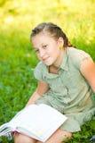Retrato del primer de la muchacha adolescente en una hierba con el libro Imágenes de archivo libres de regalías