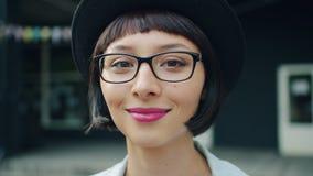Retrato del primer de la muchacha bonita joven en vidrios y sombrero que sonríe al aire libre almacen de metraje de vídeo
