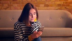 Retrato del primer de la muchacha bonita joven que hojea medios sociales en el teléfono y que sonríe feliz sentándose en el piso  almacen de metraje de vídeo