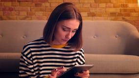 Retrato del primer de la muchacha bonita joven que mecanografía en la tableta y que sonríe feliz sentándose en el piso en un apar metrajes