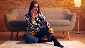 Retrato del primer de la muchacha bonita joven que tiene una conversación sobre el teléfono y que habla ocasional sentarse en el  metrajes