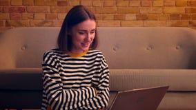 Retrato del primer de la muchacha bonita joven que tiene una llamada video en el ordenador portátil y que sonríe feliz sentándose metrajes