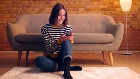 Retrato del primer de la muchacha bonita joven que usa el teléfono que se sienta en el piso en un apartamento acogedor dentro metrajes