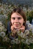 Retrato del primer de la muchacha bonita que descansa sobre campo del diente de león en Sunny Spring Day Imágenes de archivo libres de regalías