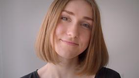 Retrato del primer de la muchacha caucásica linda joven que sonríe mirando la cámara dentro en el cuarto vacío almacen de video